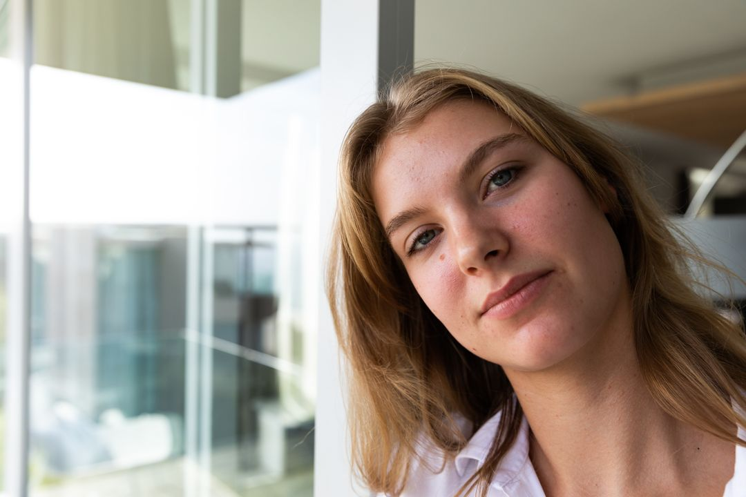 Portrait of a young Caucasian woman wearing a white shirt, standing on a balcony, looking at the camera, with her apartment in the background