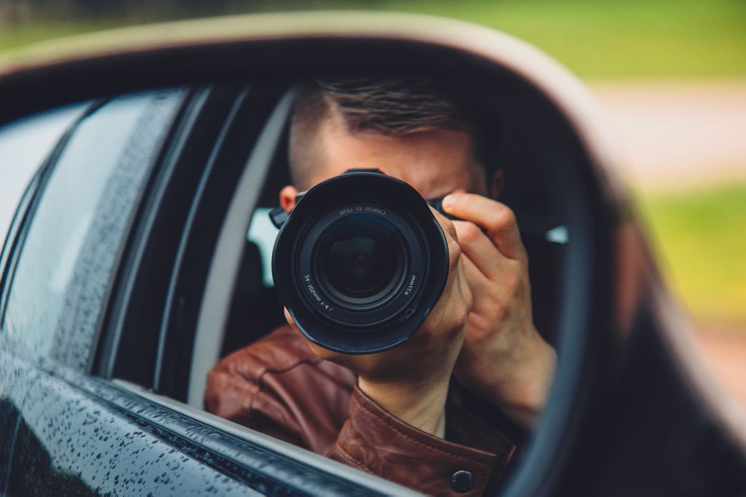 Photograph if a fashionable man taking a photo with a camera in car mirror