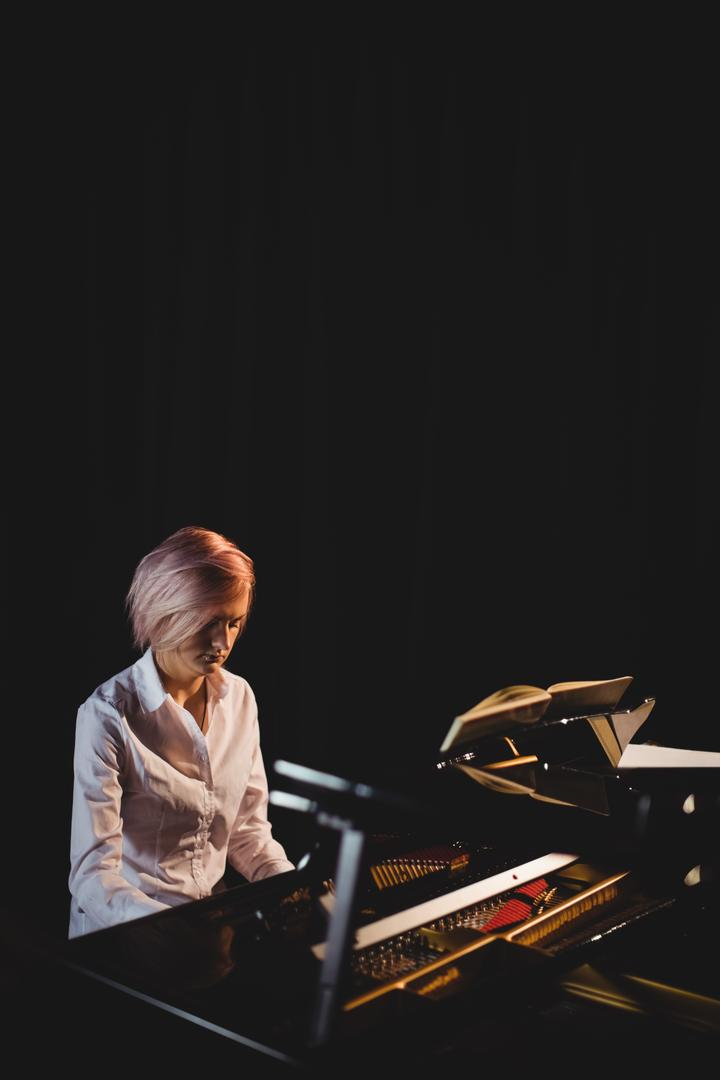 Female student playing piano in a studio Free Stock Images from PikWizard