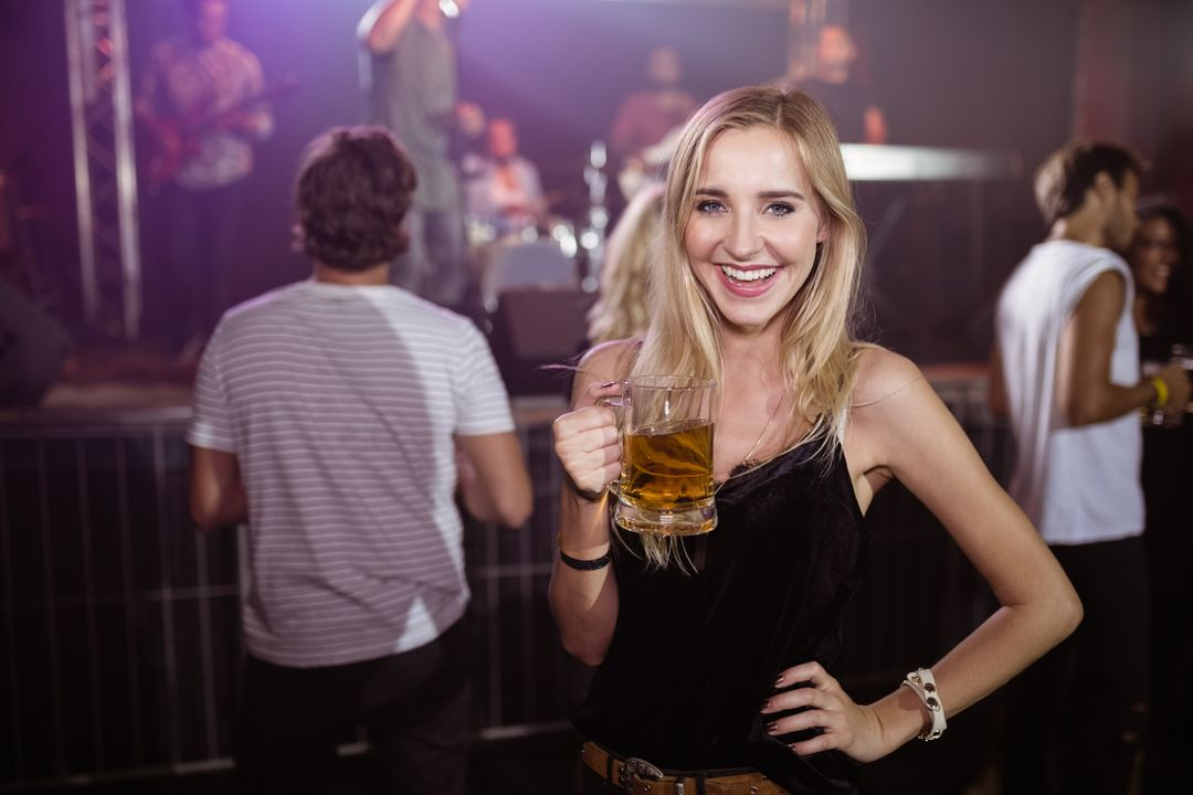 Portrait of smiling young woman holding beer mug at nightclub