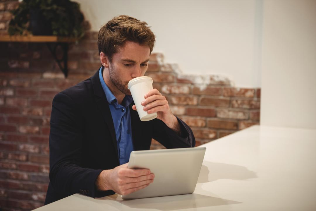 Businessman using digital tablet while having coffee in café