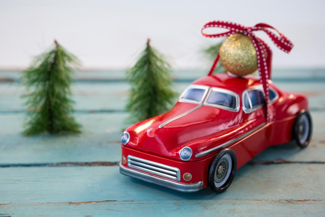 Toy car carrying christmas bauble ball on wooden plank during christmas time