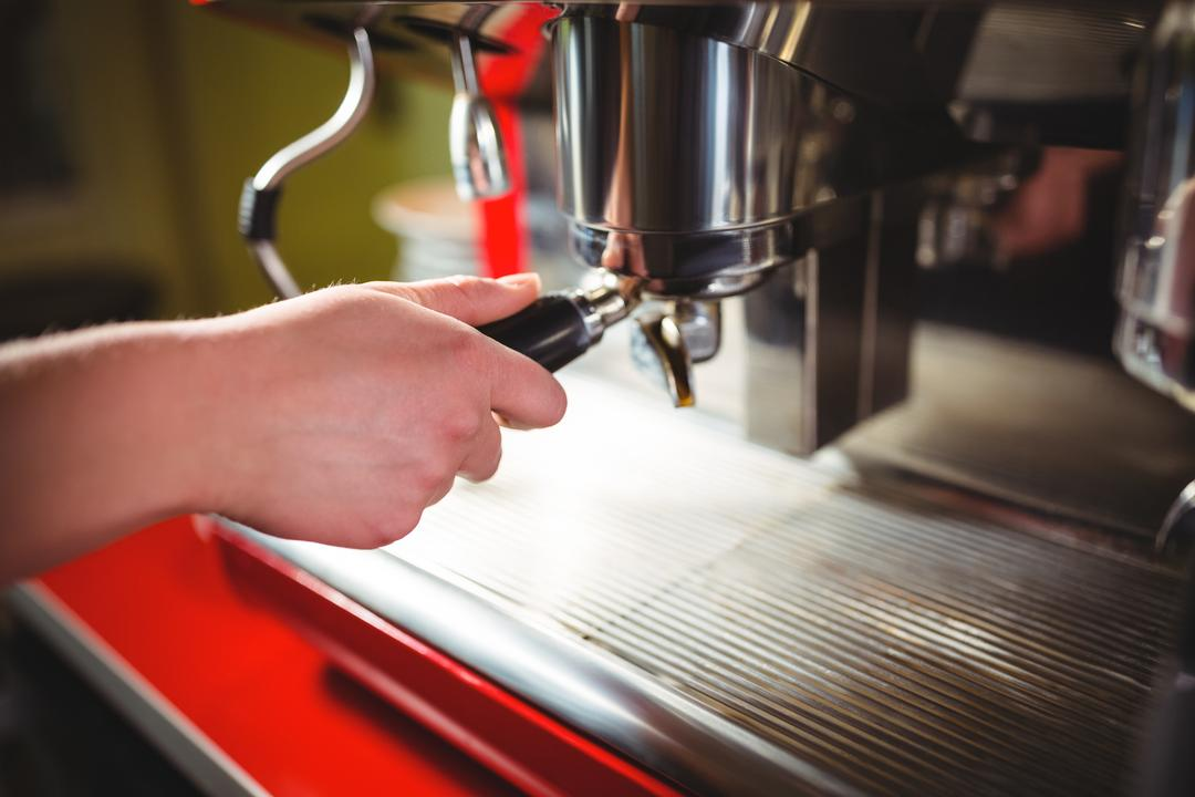 Waitress using espresso machine at counter in café