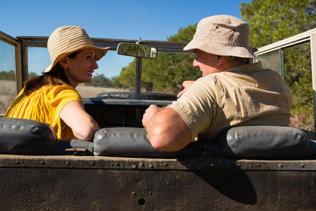 Couple talking while sitting in off road vehicle