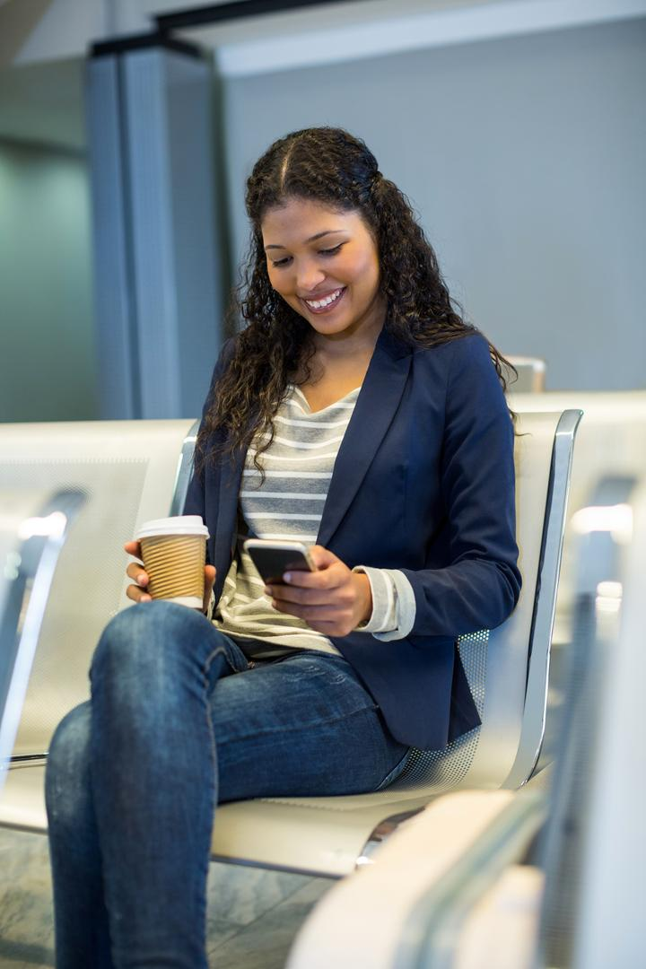 Female commuter with coffee cup using mobile phone in waiting area at airport terminal