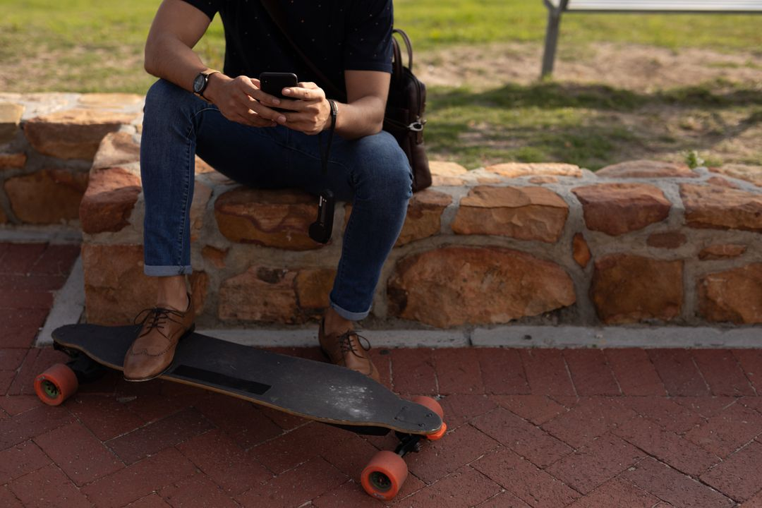 Mid section of man using smartphone with feet on skateboard