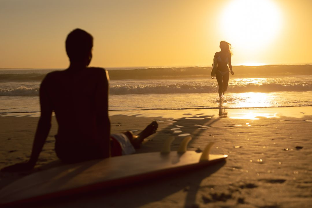 Woman running with surfboard while man relaxing on the beach during sunset