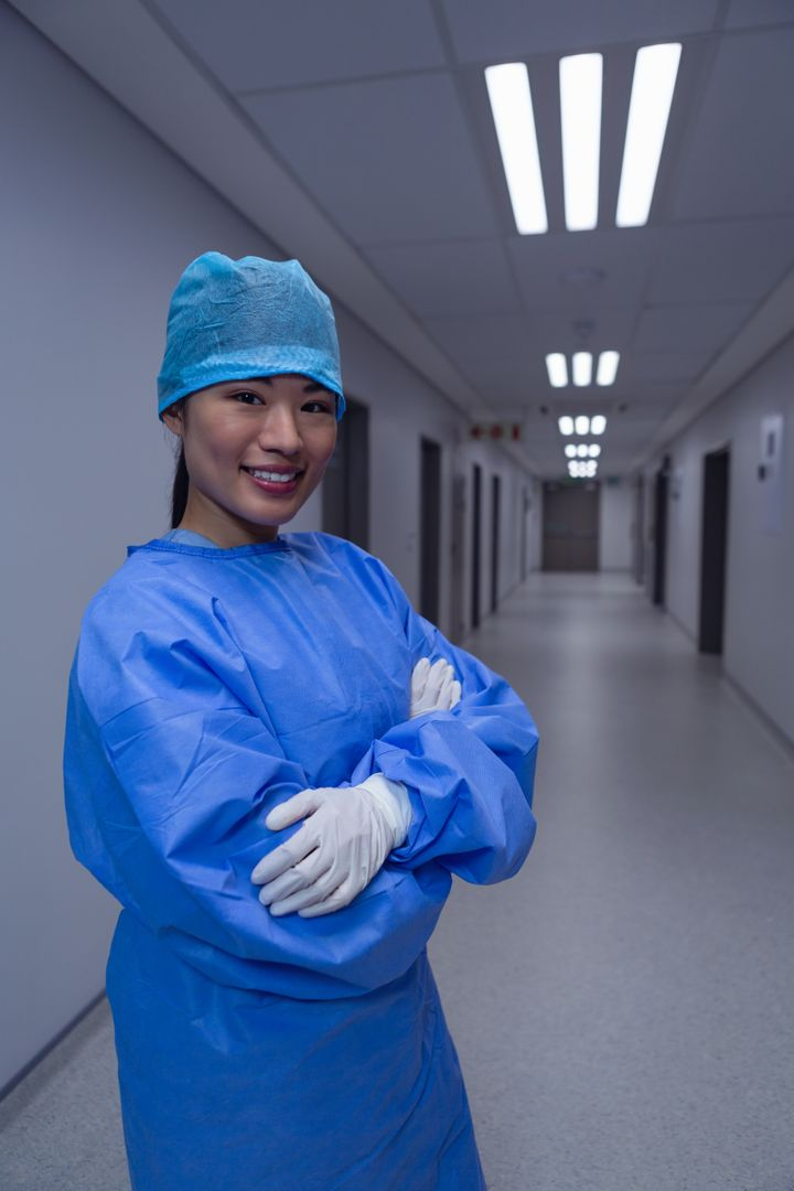 Side view of female surgeon with arm crossed standing in corridor at hospital