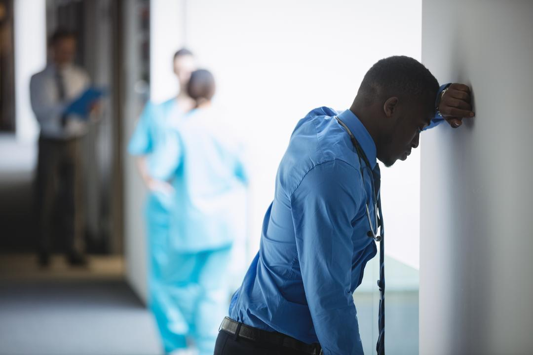 Sad doctor leaning on wall in hospital corridor