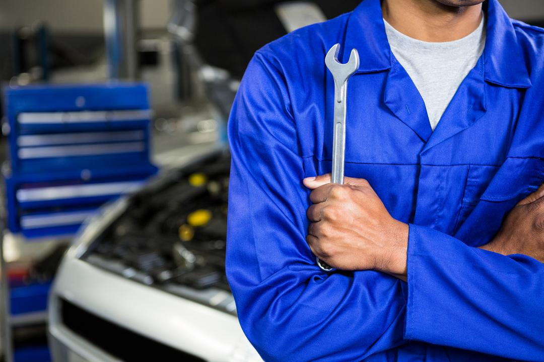 Mid section of mechanic with arms crossed holding spanner at repair garage
