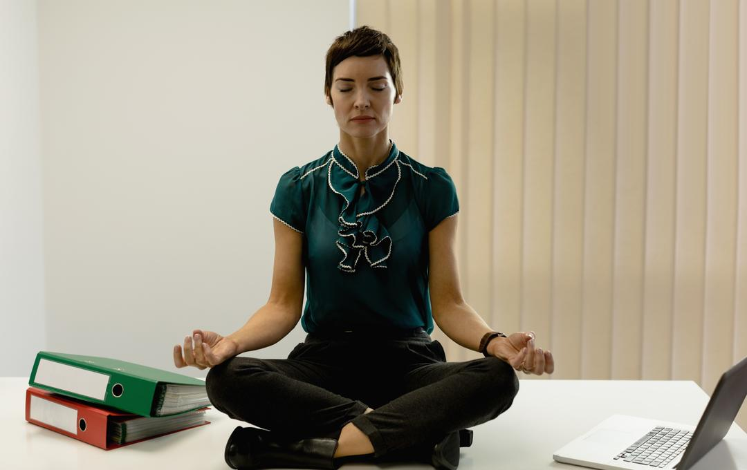 Beautiful businesswoman practicing yoga in office Free Stock Images from PikWizard