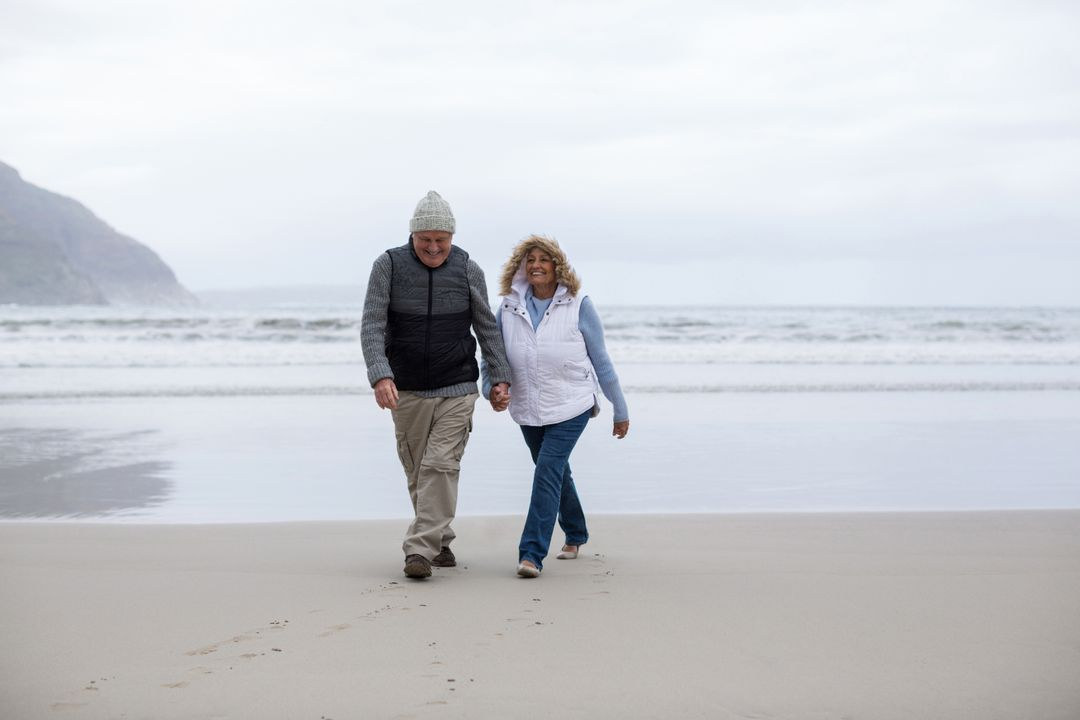 Happy senior couple walking with holding hands on the beach Free Stock Images from PikWizard