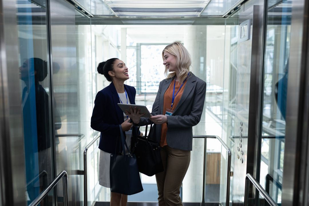Front view of happy young multi-ethnic businesswomen discussing over digital tablet in modern office elevator. They are smiling Free Stock Images from PikWizard