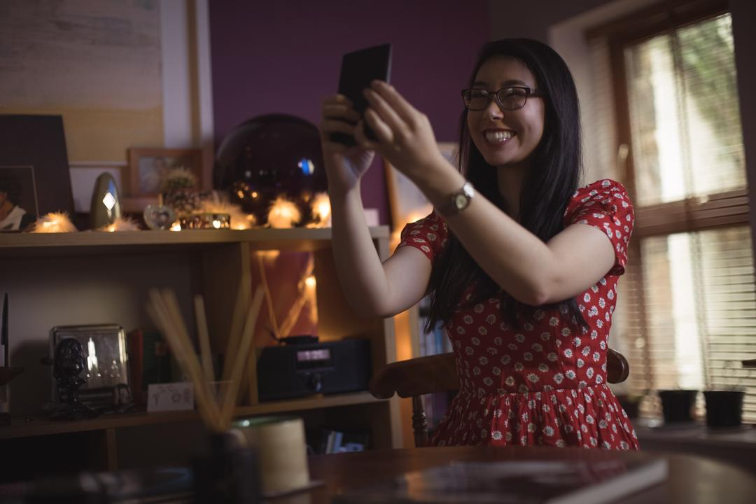 Smiling woman taking selfie on mobile phone at home