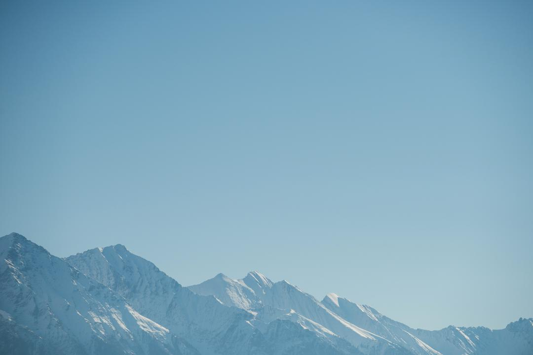 View of snowy mountain range against blue sky