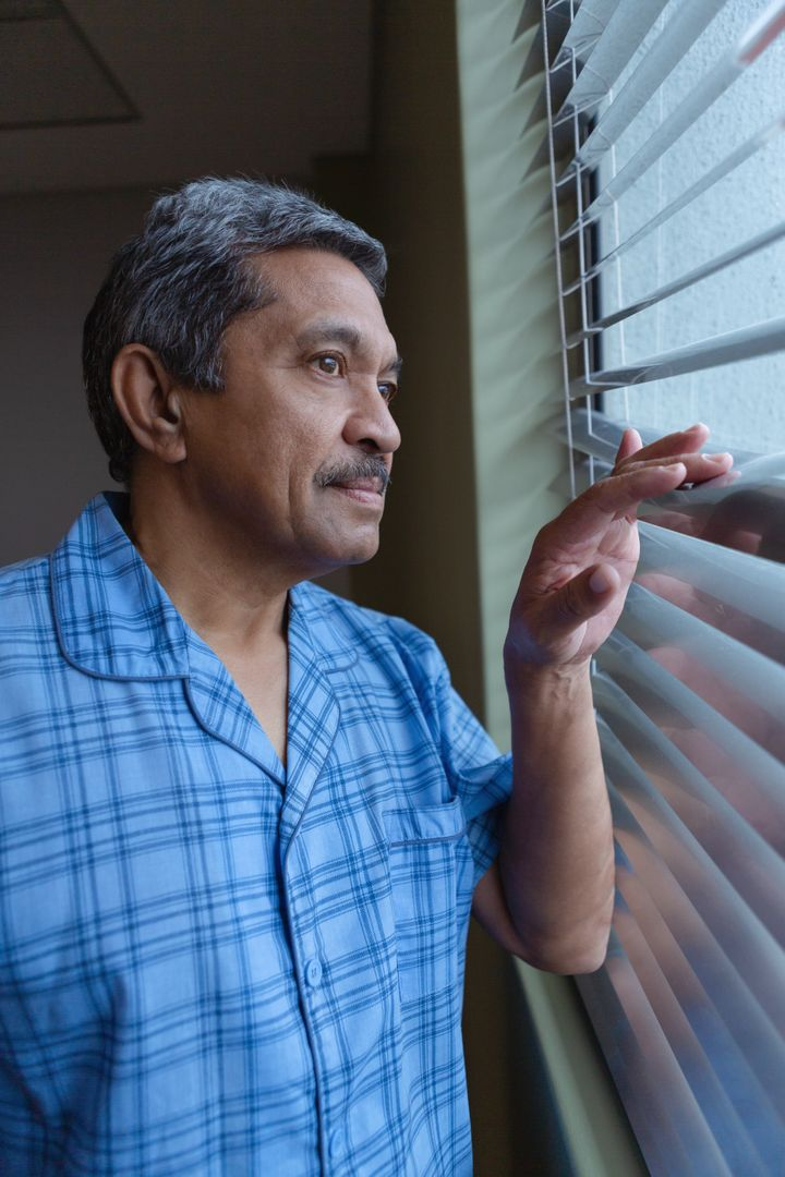 Side view of mature male patient looking through window in hospital
