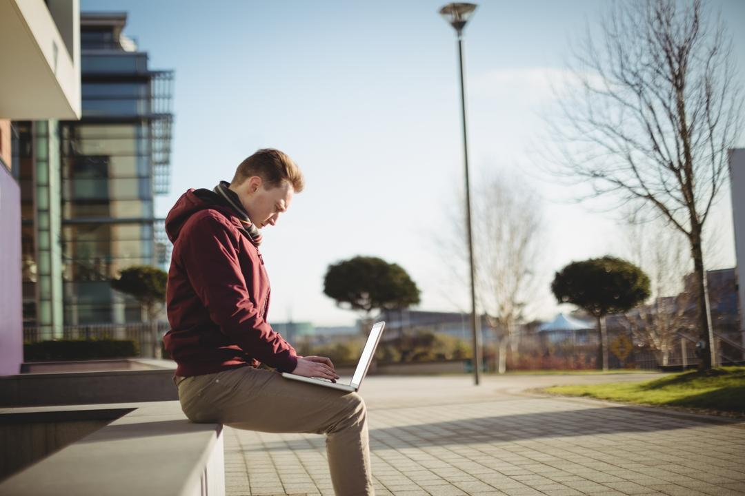 Man sitting on a wall typing onto his laptop in urban area