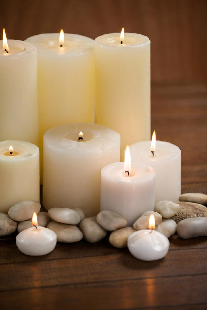 Close- up of white candles and pebbles stone on wood in spa center
