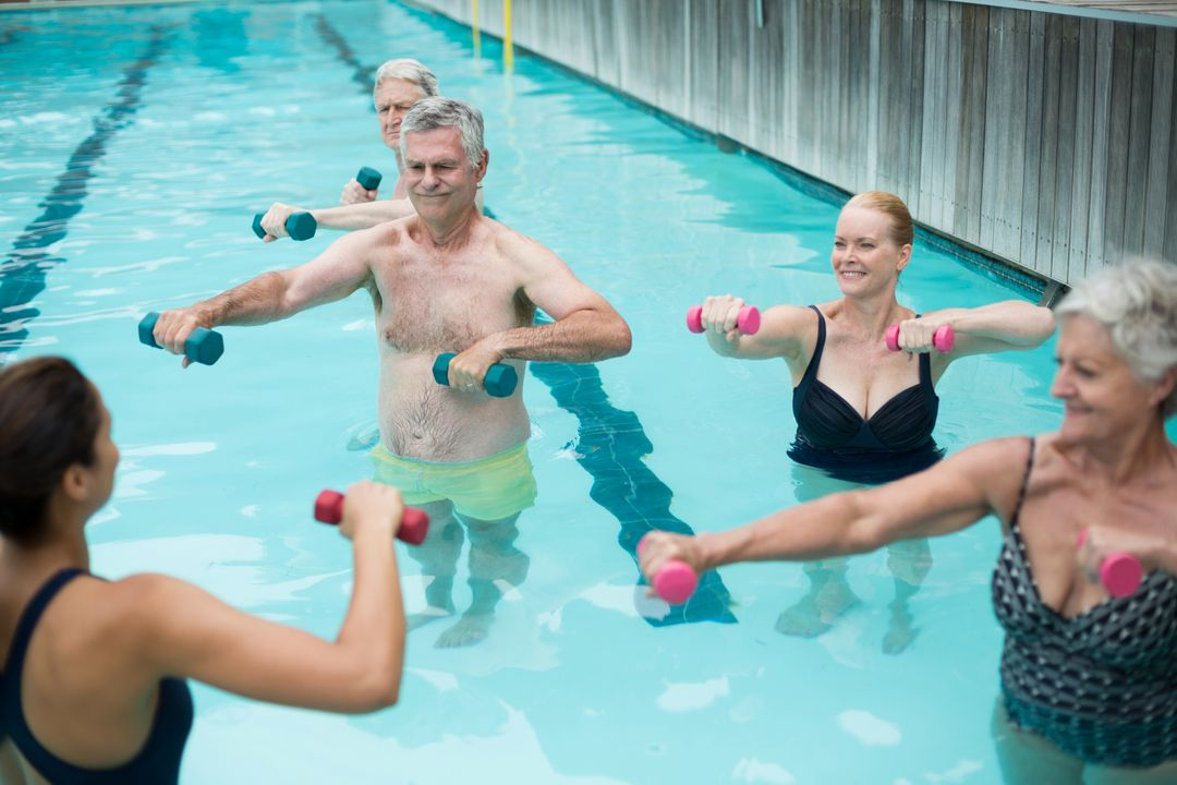 High angle view of senior swimmers and instructor lifting dumbbells in swimming pool  Free Stock Images from PikWizard
