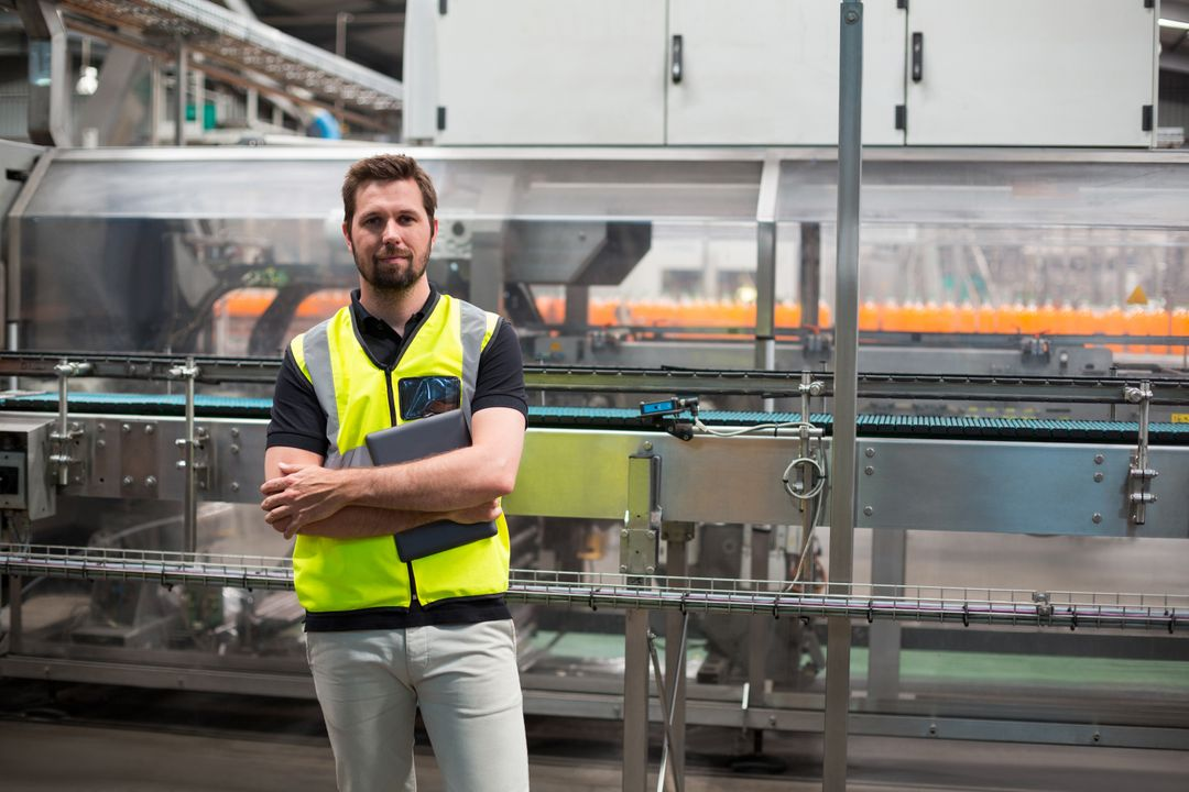 Portrait of confident factory worker standing with a digital tablet in the factory
