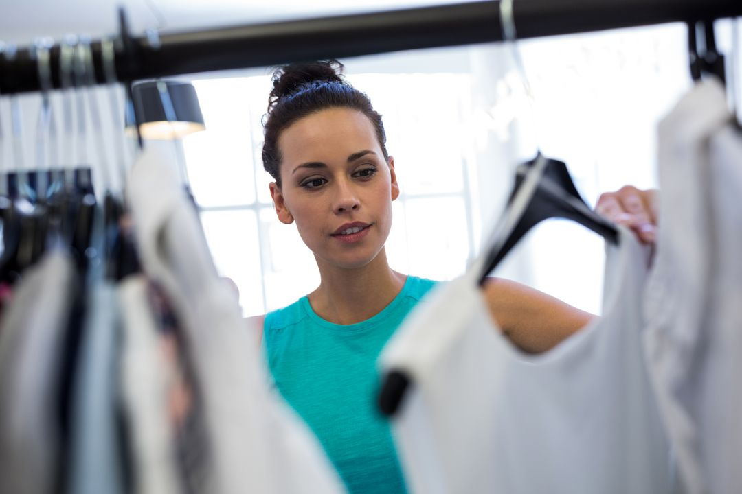 Woman in a retail store looking at clothes on a rack