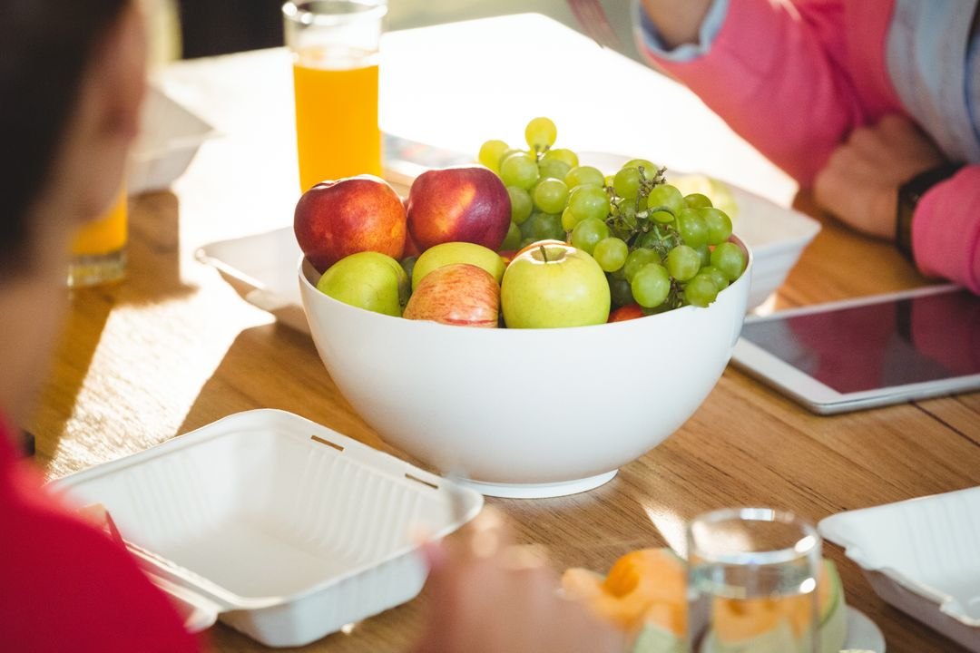 Bowl of fruits on wooden table in office Free Stock Images from PikWizard