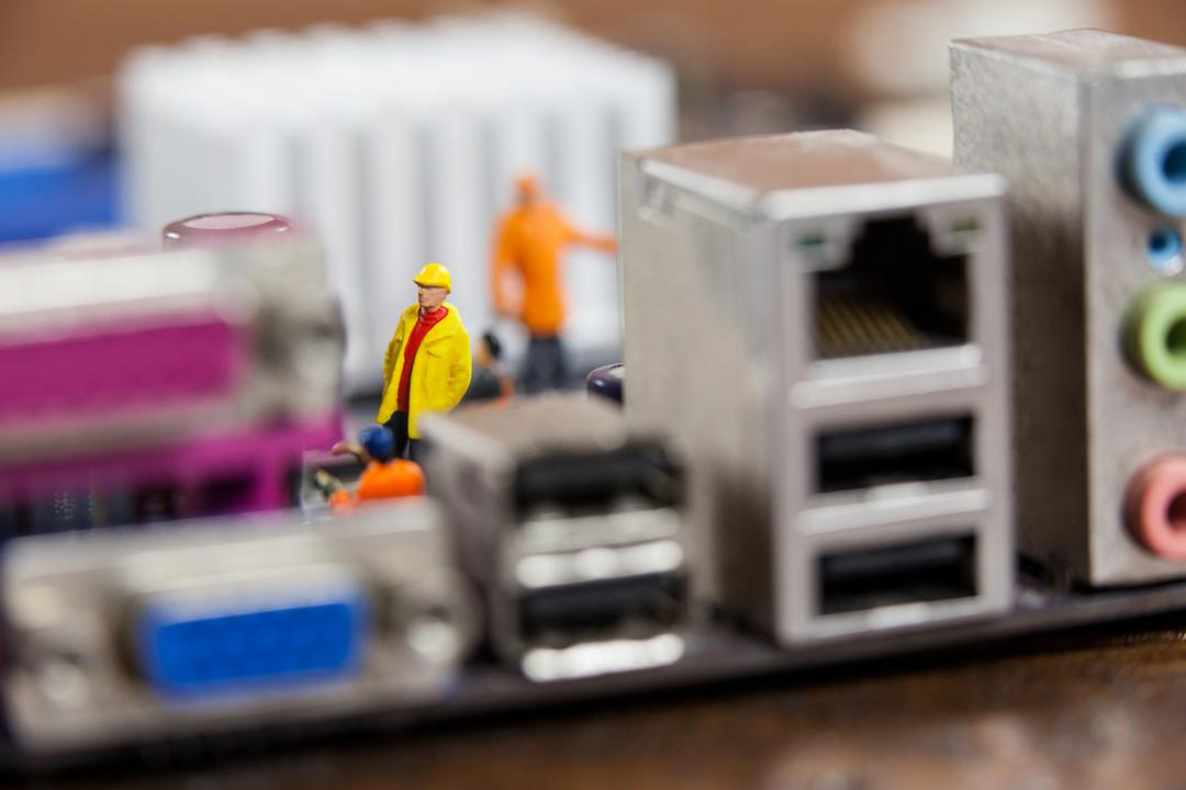 Conceptual image of miniature workers working on chip of motherboard