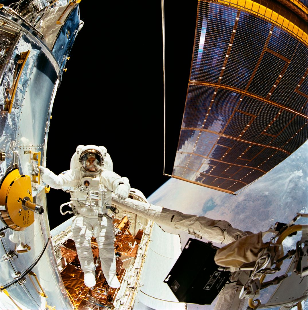 STS061-104-007 (5 Dec 1993) --- Astronaut F. Story Musgrave, holding to one of many strategically placed handrails on the Hubble Space Telescope (HST), is photographed during the first of five extravehicular activity?s (EVA) on the HST-servicing mission, aboard the Space Shuttle Endeavour.