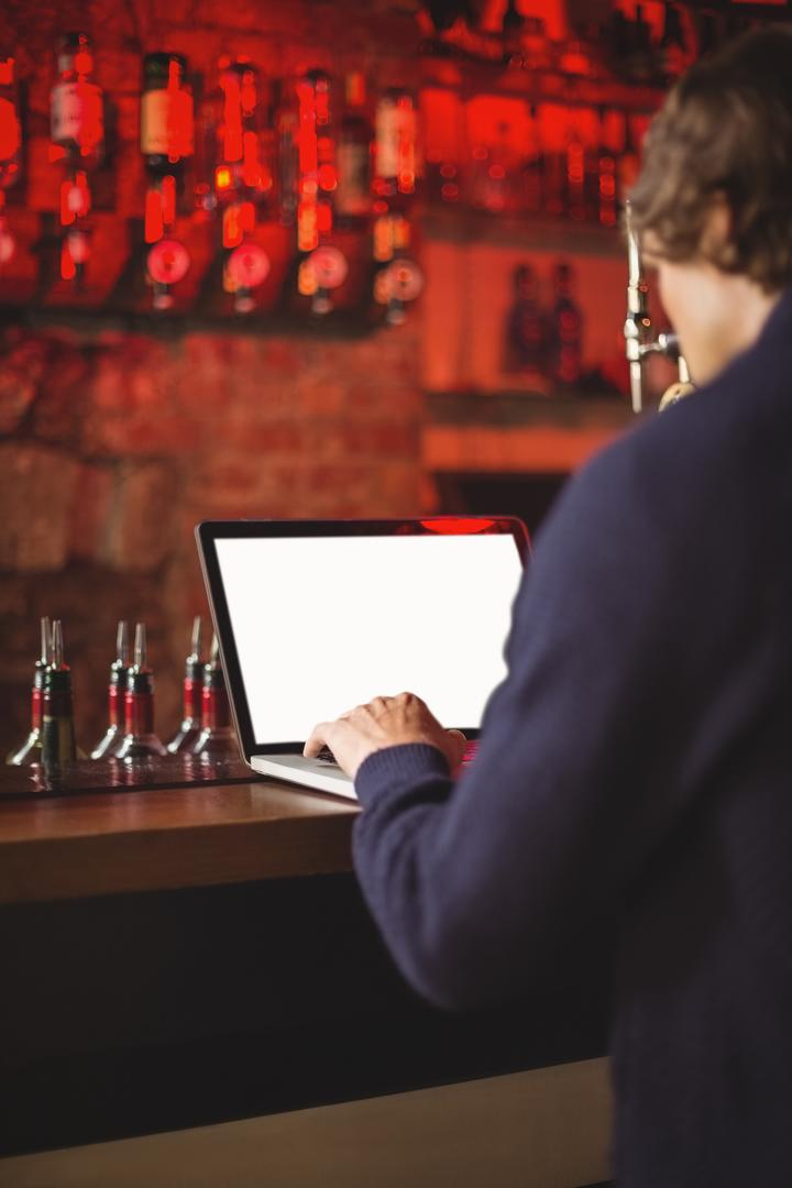 Man using laptop at bar counter Free Stock Images from PikWizard