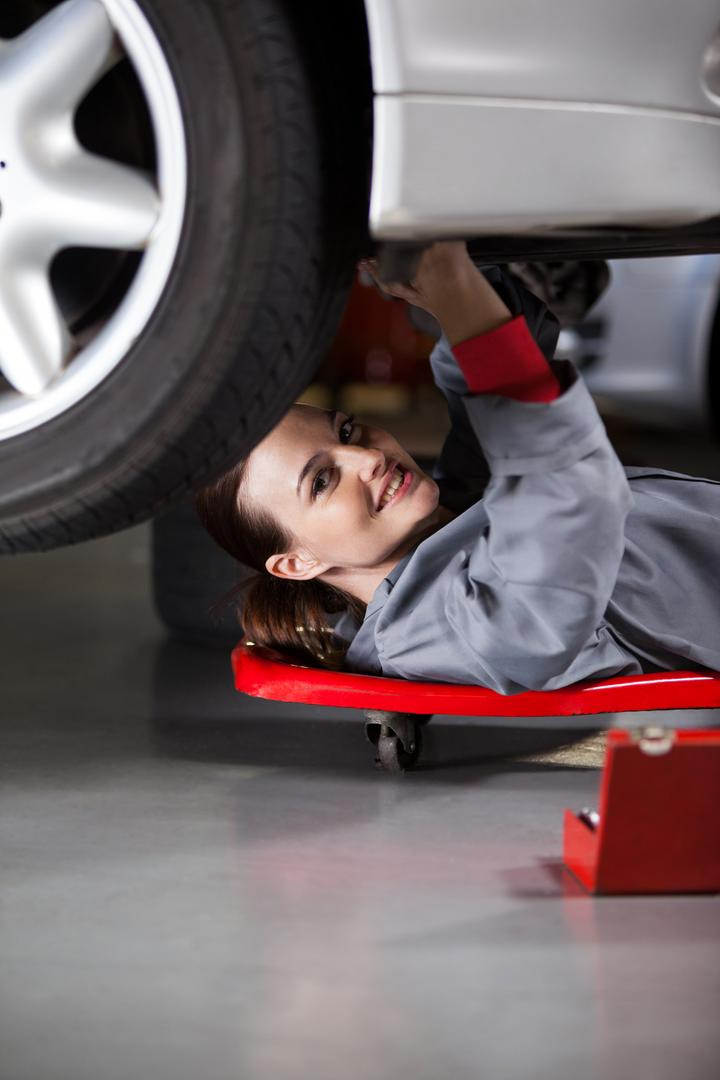 Female mechanic repairing a car at the repair garage