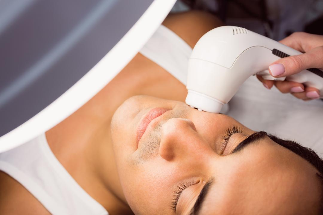 Doctor performing laser hair removal on patient face in clinic Free Stock Images from PikWizard