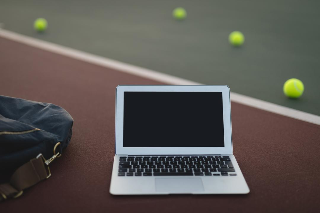 Close-up of laptop, bag and tennis ball in ground Free Stock Images from PikWizard