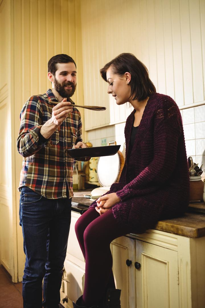 Man feeding food to woman in kitchen at home