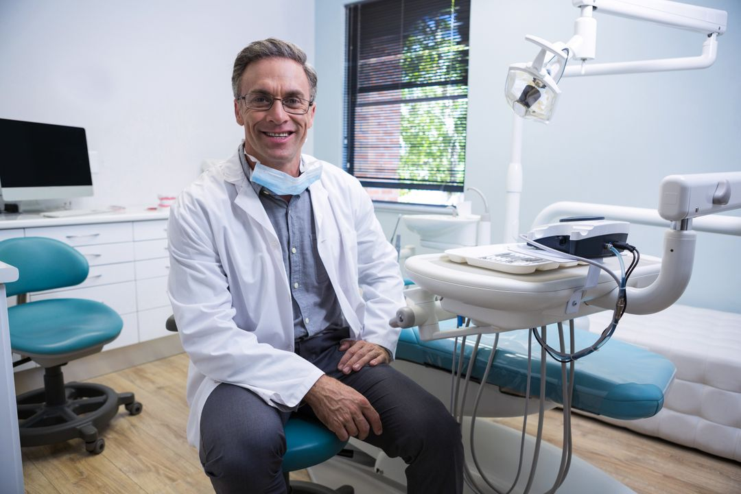 Portrait of smiling dentist sitting on chair at medical clinic Free Stock Images from PikWizard