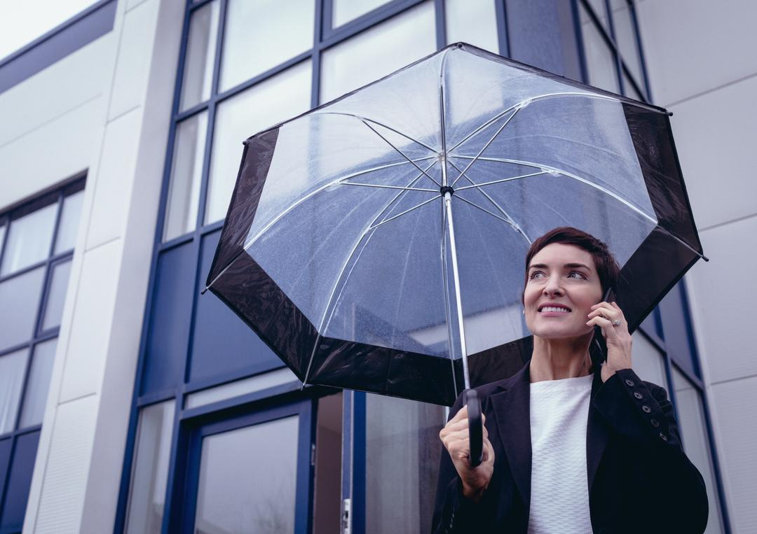 Businesswoman holding umbrella while talking on mobile phone in office premises