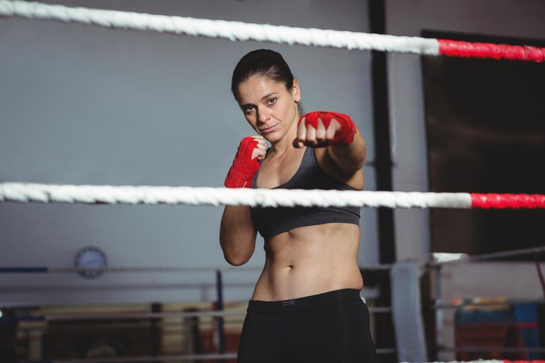 Portrait of confident female boxer performing boxing stance in fitness studio Free Stock Images from PikWizard