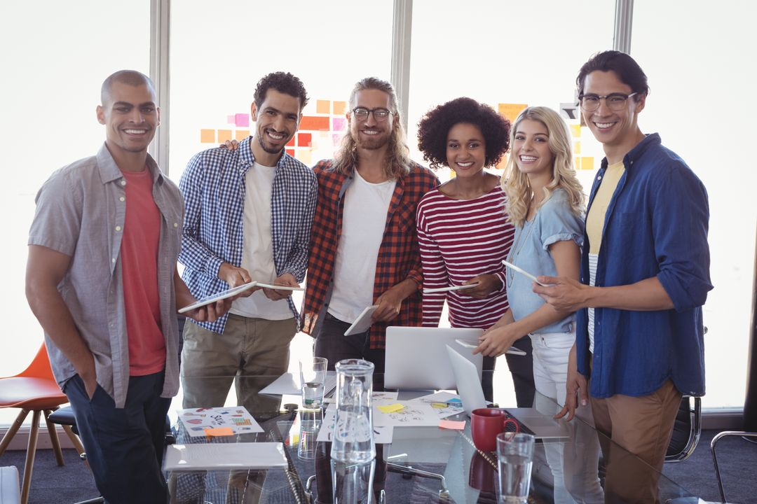 Group of 6 diverse co-workers standing at work looking at the camera