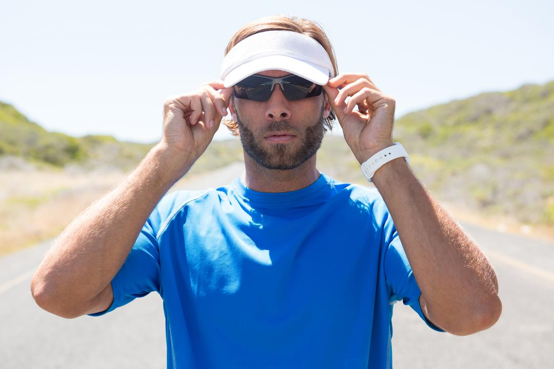 Confident male athlete wearing sunglasses on road