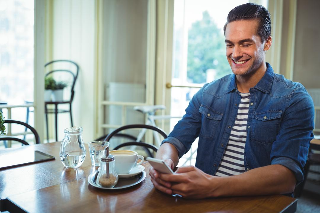 Smiling man using mobile phone with cup of coffee on table in café