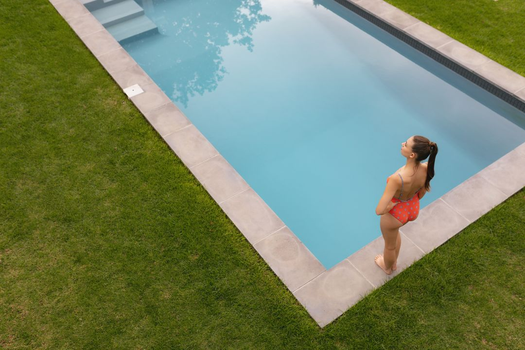 High view of thoughtful Caucasian woman in swimwear standing with hands on hip near poolside in the backyard