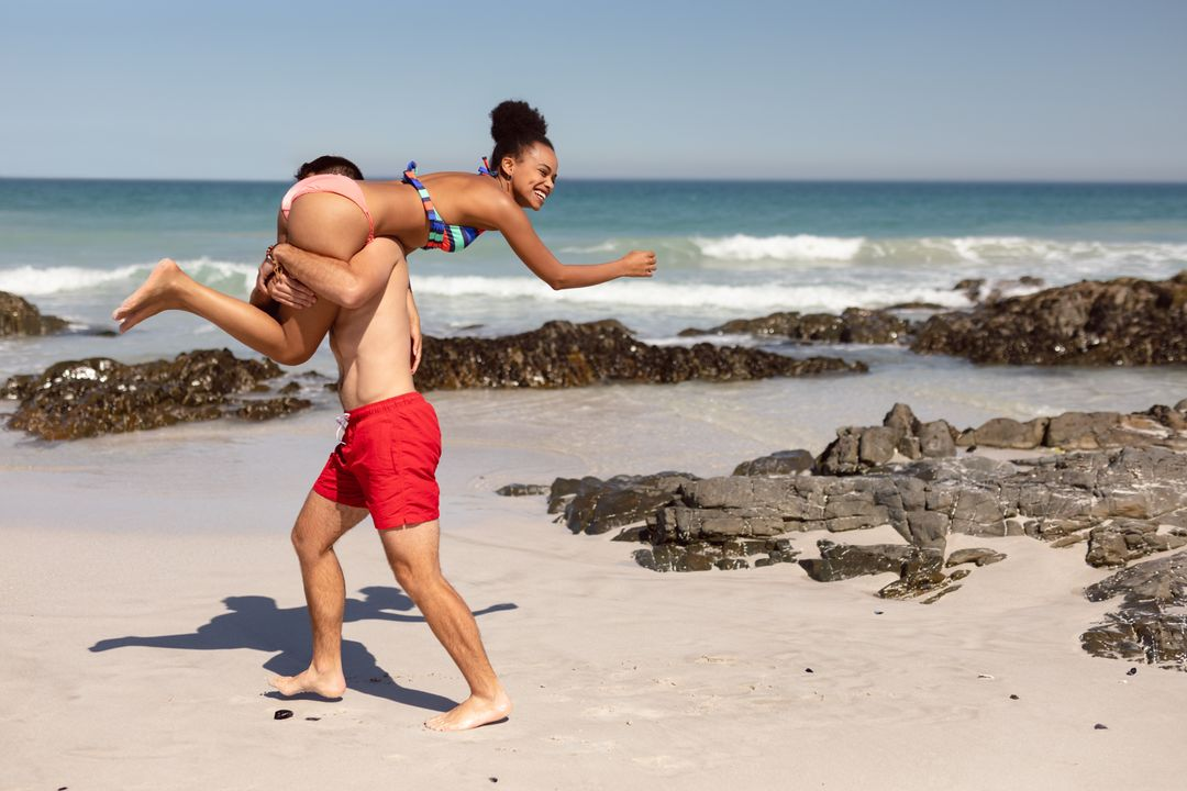 Young man carrying woman on shoulders at beach in the sunshine
