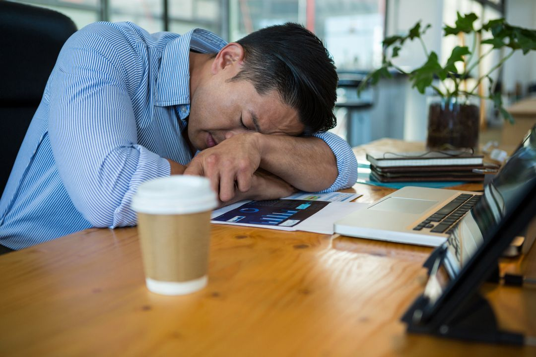 Tired business executive sleeping at desk in office