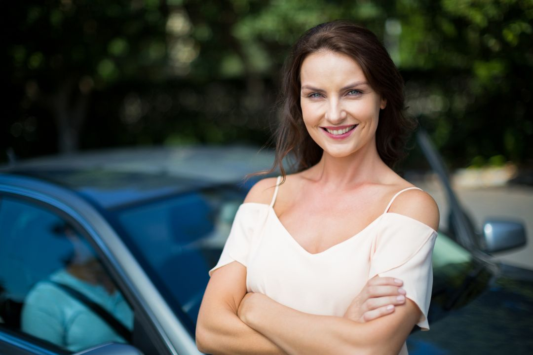 Portrait of beautiful smiling woman standing by car