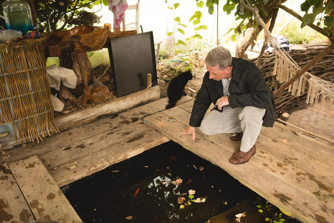 Senior man looking at fish in pond