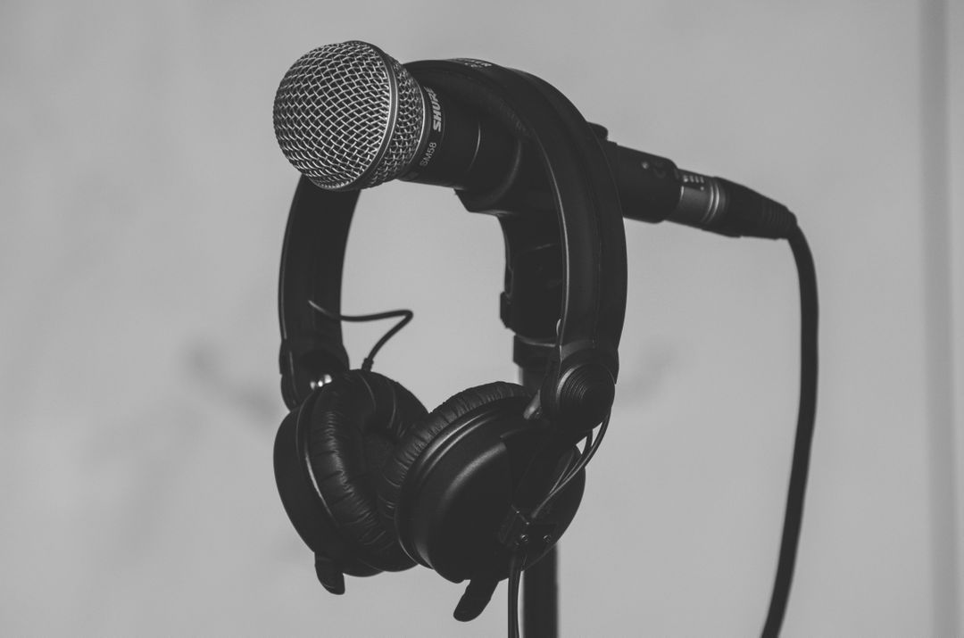 Black headphones resting on microphone in royalty free photograph.