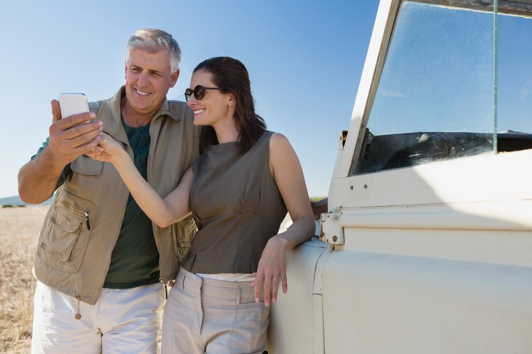 Couple looking into mobile phone by parked vehicle on field