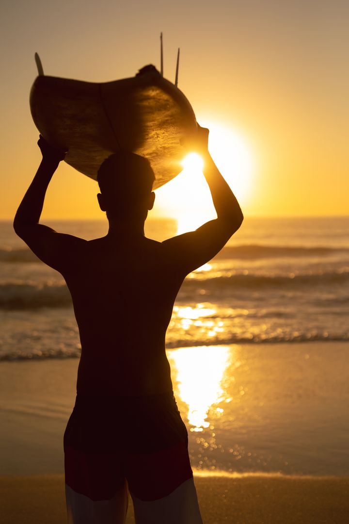 Rear view of man carrying surfboard on his head at beach