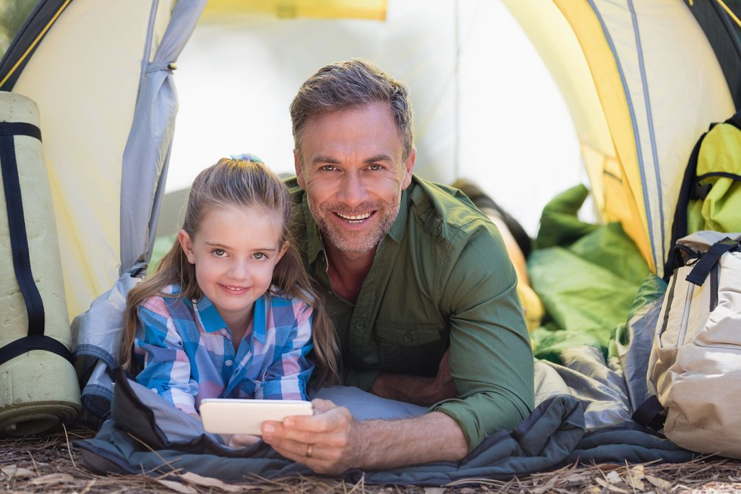 Portrait of father and daughter using mobile phone while resting in tent at campsite