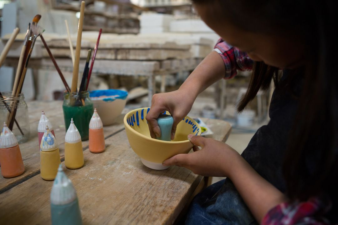Girl decorating painting bowl in pottery workshop