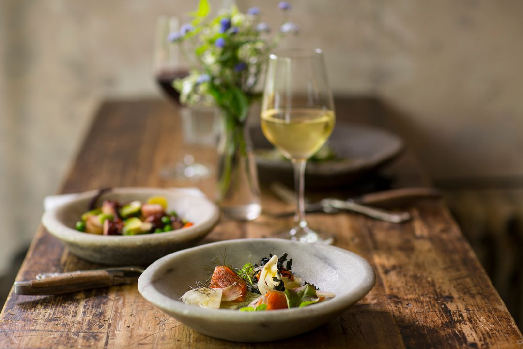 image of a beautiful meal with wine on a wooden table, with flowers for decoration